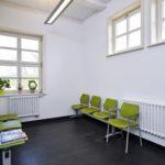 Wartezimmer, weiß mit grünen Stühlen