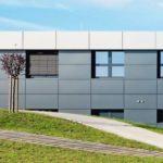Firmengebäude mit grauen Fassadenplatten und Sonnenschutz. Bild: Brüninghoff