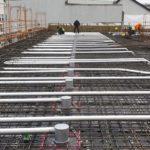 In die Betondecken werden rasterbezogen Kühlrohre aus wärmeleitendem Aluminium eingegossen