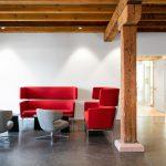 Sitzgecke in einem Foyer mit offenliegendem Holzgebälk. Bild: Feco-Feederle