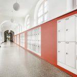 Im Verbindungsgang zwischen Alt- und Neubau setzten die Architekten ein klares Rot ein. Bild: Fermacell