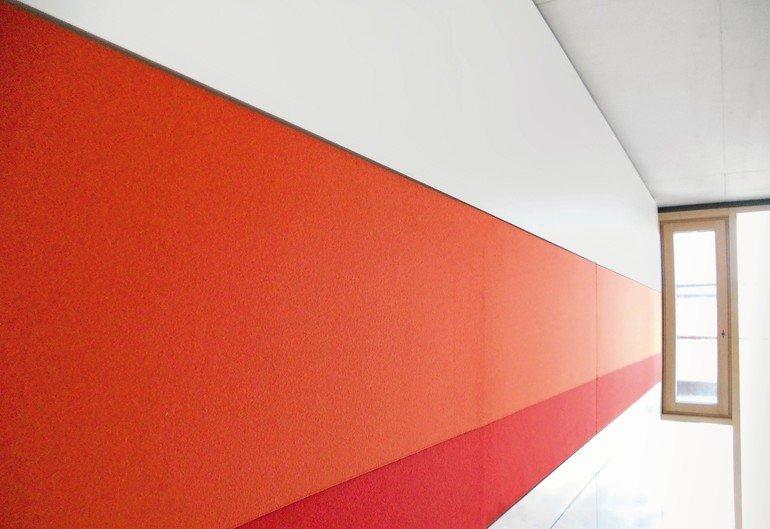 Der textile Absorber ist in eine Vollwand integriert und mit seinen Möglichkeiten zur Farbkomposition zugleich Teil der Raumgestaltung. Bild: Nikolay Kazakov/feco