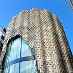 Die neue Aluminiumfassade in Schindeloptik formt nun einen großen, einladenden Bogen und nimmt dem Gebäude aus den 1980er-Jahren die optische Massivität. Bild: Pohl Facade Division