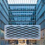 """Lichtes Atrium: In der """"Wolke"""" lassen die teilgeöffneten, rautenförmigen Lamellen Licht in die Konferenzräume. Unten ermöglichen die geöffneten Schiebewände freien Durchgang. Bilder: Solarlux GmbH"""