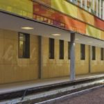 Innenhof mit Säulengang, bunte Fassade aus Glaselementen. Bild: Fabrino