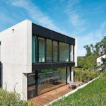 Helle Leichtbeton-Wand und Glasflächen vor Rasen.