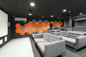 Kinosall mit dekorativen Wandpaneelen in Wabenoptik für verbesserte Akustik. Bild: Knauf AMF