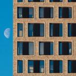 Fensterscheiben in der Fassade werden von braunen Flächen gerahmt.