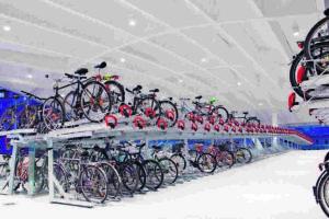 Hell erleuchteter Fahrradparkplatz mit zweistöckigen Fahrradständern. Bild: Gronard