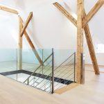 Dachboden eines renovierten Fachwerkhauses mit zentralem, glasverkleideten Treppenaufgang. Bild: Glas Marte