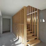 Das warme Holz eines Treppenaufgangs trifft auf Betonoptik. Bild: Wurm + Wurm
