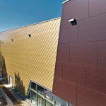 Die Titanzinkrauten bilden durch Spiegelung und Glanz einen spannenden Kontrast zur dunklen Fassade aus HPL-Platten. Bild: Rheinzink