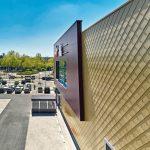 Frontfassade eines Flachdachgebäudes mit goldenen Rauten verkleidet, der vorspringende, linke Teil der Fassade ist mit dunkelroten Platten verkleidet. Bild: Rheinzink