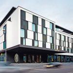 Die strahlend weiße Fassade des Roomers Baden-Baden wird schachbrettartig von geschosshohen Fenstern strukturiert. Bild: Roomers Baden-Baden