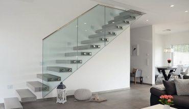 Charakterstarke Raumskulptur: Kragarmtreppe von Spitzbart mit scheinbar schwebenden Stufen aus Betonwerkstein sowie einem punktgehaltenen Glasgeländer. Bild: Spitzbart