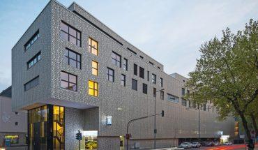 Aluminiumpaneele wurden eloxiert und perforiert: Eine glänzende Metallfassade schirmt das Parkhaus mit Wohnüberbauung ab. Bild: Tobias Kern