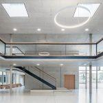 Lichtes, großzügiges Foyer mit Treppe und Blick auf den Gebäudeteil mit den Fachräumen. Bild: Hörmann / Schörghuber