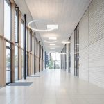 Die verglaste Pausenhalle ist Entree für den Saal und zugleich Pausenraum mit hoher Aufenthaltsqualität bei Regenwetter. Bild: Hörmann / Schörghuber
