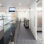 Eine Vollspan-Schiebetür führt in die Küche. Sie liegt platzsparend an der Wand und gibt im geöffneten Zustand die volle Durchgangsbreite frei. Bild: Hörmann / Schörghuber