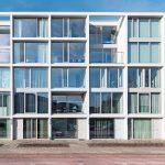 Fünfgeschossiger Riegel mit streng gerasterter Frontfassade, die durch raumhohe Glasflächen mit lichtweißen Fassadenstützen und -trägern geprägt wird. Bild: Stijn Poelstra