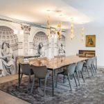 Essen mit Stil: In der Tapetenwand mit augenzwinkerndem Neoklassizismus sind Schiebetüren verborgen, hinter denen sich Stauraum versteckt. Bild: Eclisse