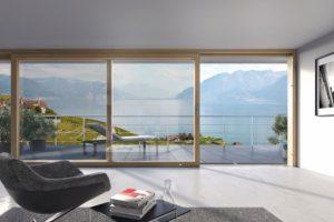 Wohnzimmer mit großer Schiebetür mit Blick auf Veranda und Bergpanorama
