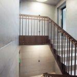 Treppenhaus mit Sichtbetonwänden und Metallgeländer mit Holzhandlauf. Bild: PSS Interservices AG