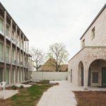 Innenhof mit Holzgalerien auf der linken und einem sanierten Backsteingebäude auf der rechten Seite.