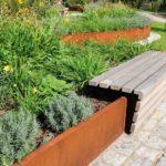 Holzbank auf Cortenstahlumrandung eines Gartenbeets.