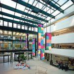 Das zentrale Atrium mit Glasdach dient als Eingangsbereich mit Café. Bild: Andreas Frisch; GSP Architekten