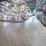 Der elegante, graue Boden mit sichtbaren Donaukieseln tritt dezent hinter das Warenangebot zurück. Bild: HeidelbergCement/Stefan Fuchs