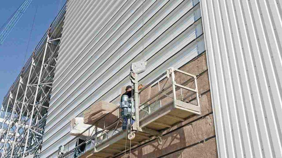 Isolierschicht wird an der Fassade einer Industriehalle angebracht. Bild: Knauf Insulation