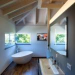Eine Ganzglasecke sorgt im edel ausgestatteten Bad dafür, dass sich von der Badewanne aus der unverbaute Ausblick genießen lässt. Bild: Kneer-Südfenster