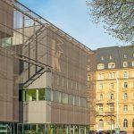 Die bronzefarbene Metallfassade definiert die Kubatur der Gebäudes und lässt gleichzeitig ausreichend Licht ins Innere. Bild: Constantin Meyer Photographie