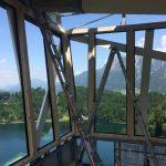 Ausblick aus dem oberen Warteraum einer Skiflugschanze, See und Bergpanorama im Hintergrund. Bild: Holzverarbeitung Bietsch