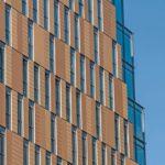 Projektspezifisch gefertigt: die lachsfarbenen Fassadenfliesen in drei Terrakotta-Nuancen mit ebener oder rillierter Oberfläche. Die Fassade wird so dezent rhythmisiert. Bild: Agrob Buchtal / Simon Hadley