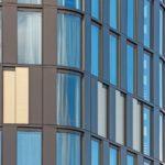 Hier zeigt sich die Intelligenz der Fassade: Je nach An- oder Abwesenheit des Gastes öffnen oder schließen die goldfarben eloxierte Stahl-Schiebeläden. Bild: Ossip van Duivenbode