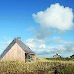 Ausblicke wie beim Dünenwandern bieten variantenreich geschnittene Öffnungen in einem Ferienhaus auf der Nordseeinsel Terschelling. Bild: Filip Dujardin