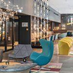 Die Lounge greift an der Wand das Berliner Fashion-Thema mit Arbeiten von HTW-Modestudentinnen auf. Bild: Motel One