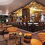 """Die Bar in Zürich spielt farblich mit dem Motiv der Schweizer Schokolade, ergänzt vom goldenen """"Schokoladenpapier"""" an der Decke oder den Hockern in Form von Schichtpralinen. Bild: Motel One"""