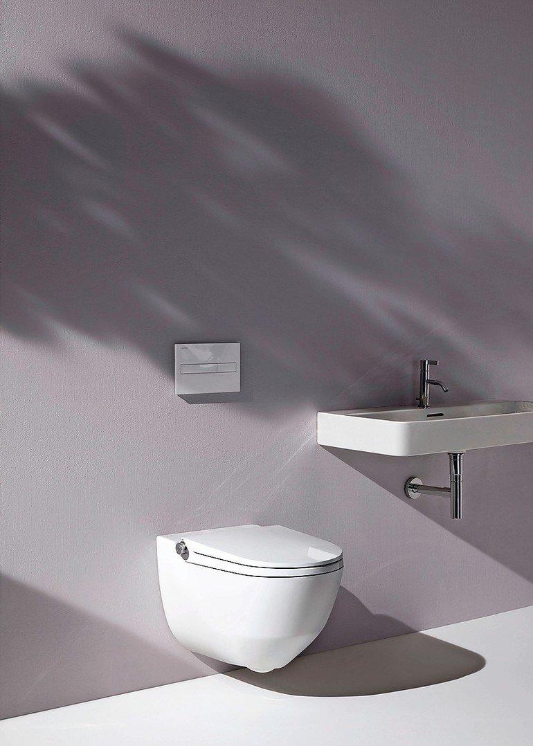 Modernes Badezimmerensemble mit Toilette und Waschbecken. Bild: Laufen