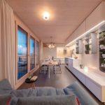 Der großzügig wirkende Küchen-, Ess- und Wohnbereich der größeren Wohnung profitiert von platzsparenden Schiebetüren und Zargenführungen – und vom weiten Panoramablick. Bild: Häfele