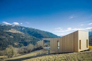 Auf einem Hangwiesengrundstück im österreichischen Trebesing hat ein Münchner Architektenpaar ein kompaktes Minimalhaus in Holzfertigteilbauweise errichtet.