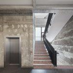 Auch in den Treppenhäusern wurden die nackten Betonwände wieder freigelegt, die Treppen in rotem Terrazzostein blieben erhalten. Bild: GBP Architekten / Anastasia Hermann