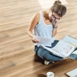 Young_woman_sitting_on_wooden_floor_with_file_folder_and_laptop