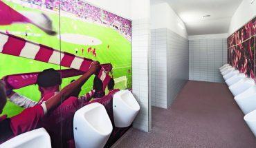 Die Sanitärbereiche des Düsseldorfer Fußballstadions wurden mit farbig bedruckten Motivwänden und WC-Kabinen in den Vereinsfarben neu gestaltet. Bilder: Schäfer Trennwandsysteme