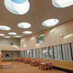22 runde Flachdachfenster in geschwungenem Deckenverlauf eines Kindergartens