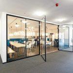 Rahmenlose, zweiflügelige Ganzglastür aus Brandschutzglas als Zugang zu einer Teeküche
