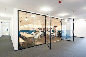 Rahmenlose, zweiflügelige Ganzglastür aus Brandschutzglas als Zugang zu einer Teeküche. Bild: Promat