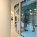 Gefällige Glasfassade mit gebogenen Scheiben und Alu-Lamellen
